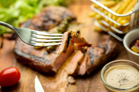 T-Bone Beef Steak on wooden board.  Beef Steak Dinner and French fries. Stock Photo
