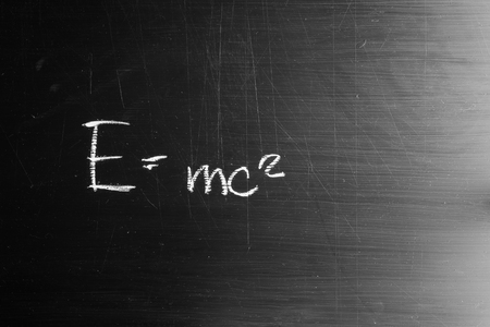 E equals mc squared drawn with white chalk and copy space on blackboard.