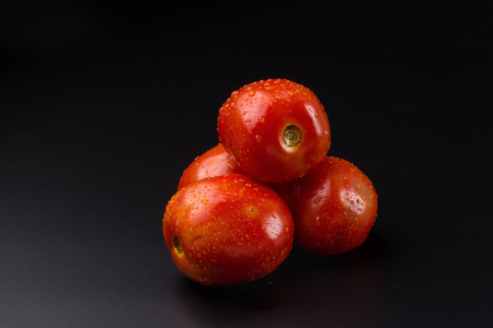 Ripe red tomatoes isolated on bjack background. Stock Photo