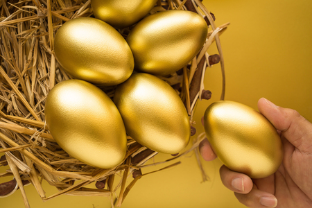 Financial success. Man holding a golden egg. Golden Egg on golden background.