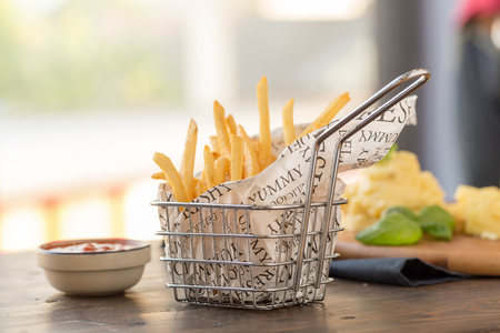 French fries with ketchup on wooden background.