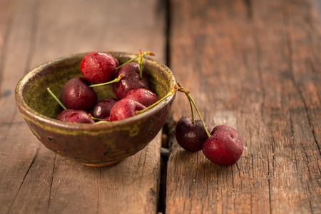 Bowl of Cherries. Red cherries in a bowl on wooden background.