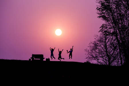 Silhouette of people jumping against under a sunset. Stock Photo