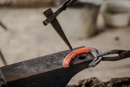The blacksmith kicks a horseshoe close up.