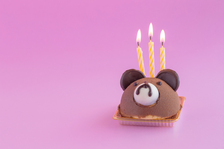Brown Teddy Bears Head Chocolate Chiffon Cake with candles on a pink background.