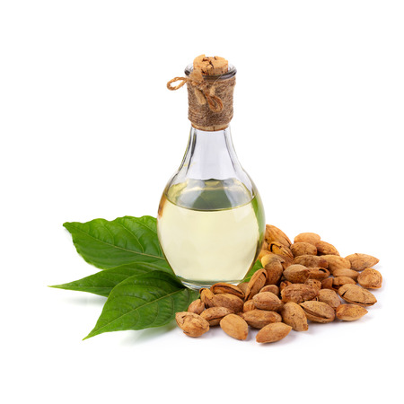 Bottle of almond oil and almonds isolated on white background.