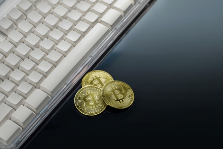 Bitcoin physical Bitcoin-Cryptocurrency on keyboard. Business concept. Stock Photo