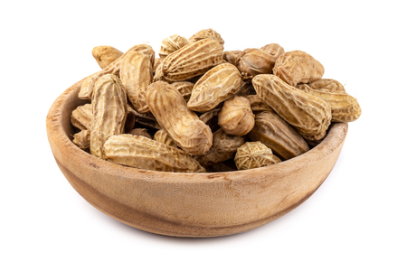 Dried peanuts in wooden bowl isolated on a white background.