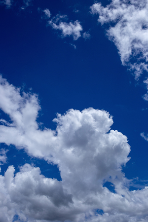 White fluffy clouds in the blue sky background.