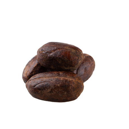 Dry nutmeg spice isolated on a white background.