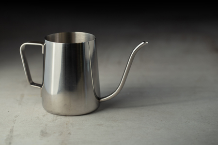 Stainless steel pitcher on the cement table.