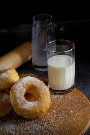 Donuts with sugar on a wooden plate on a dark table background