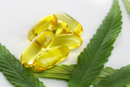 Cannabis essential oil Capsules with cannabis leaves on white background. 版權商用圖片