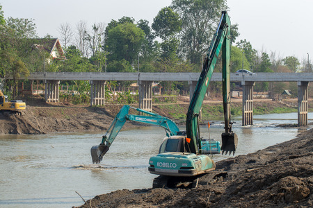 LAMPANG, THAILAND – MAY 3, 2019: Yellow Backhoes digging sand with shovels from the Wang River to support the water in the rainy season. Editorial