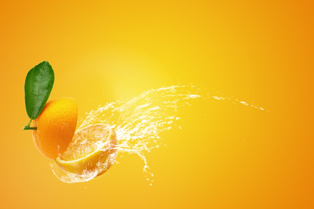 Water splashing on Fresh Sliced ​​oranges and Orange fruit over Orange background 免版税图像