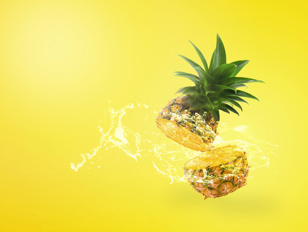 Water Splashing on Fresh Pineapple is tropical fruit isolated over yellow background.
