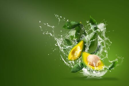 Water splashing on Fresh Sliced Green avocado isolated over the Green background.