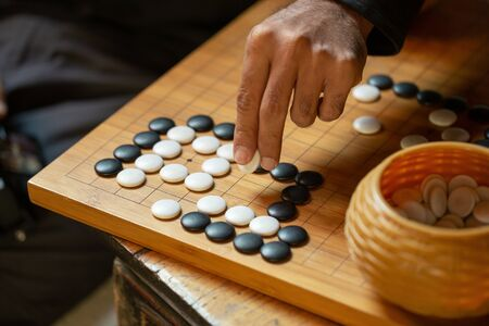 Go board game playing. A competitor is placing a marble piece on a Go board game