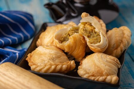 Homemade chicken Curry puffs on wooden table.