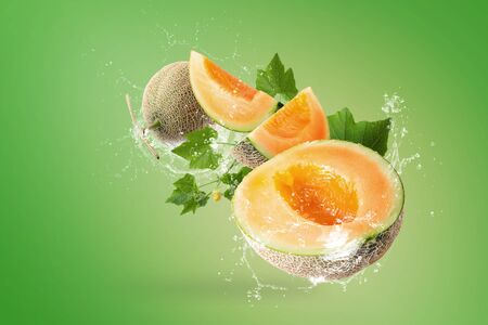 Water splashing on Sliced of Japanese melons on green background.