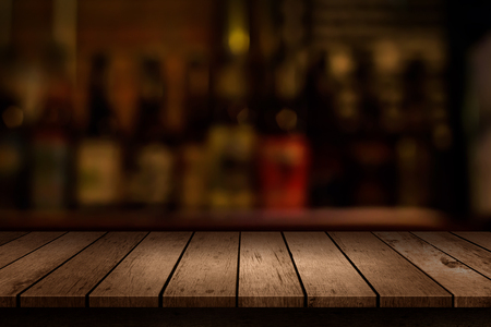 wooden table with a view of blurred beverages bar backdrop 免版税图像 - 53928171