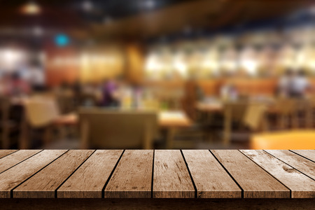 resturant: wooden table in blur resturant lights background Stock Photo