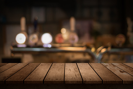 vaso vacio: wooden table with a view of blurred beverages bar backdrop