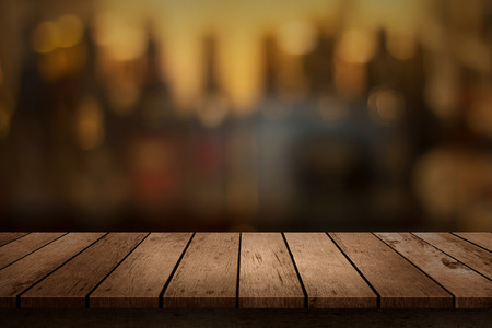 wooden table with a view of blurred beverages bar backdrop Banco de Imagens - 61110367