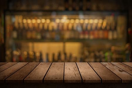 barra de bar: mesa de madera con una vista de bebidas borrosa barra de telón de fondo