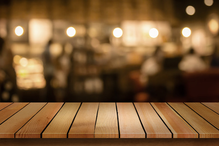 Wood table top on blur bokeh cafe background can be used for display or montage your products