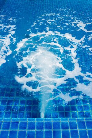 Massage and spa swimming pool with bubbles blue water.