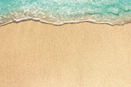 Olas suaves con espuma de océano azul en la playa de arena Foto de archivo