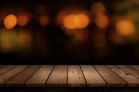 Holztisch mit Blick auf die verschwommene Kulisse der Getränkebar. Verwischen Sie Café und Restaurant mit abstraktem Bokeh-Lichthintergrund. Zum Erstellen einer Montageproduktanzeige Standard-Bild