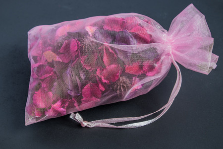 Potpourri bag on black background with pink ribbon
