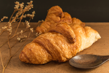 croissant bakery on wood table with Wooden Spoon_ Stock Photo