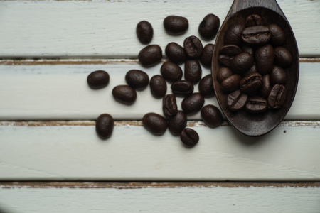 Roasted coffee beans with wooden Spoon on white wood Stock Photo