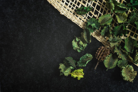 potpourri of dried aromatic flowers on weave of rattan, black background