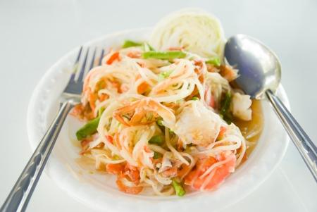 Papaya salad with horse crab on the white foam dish photo