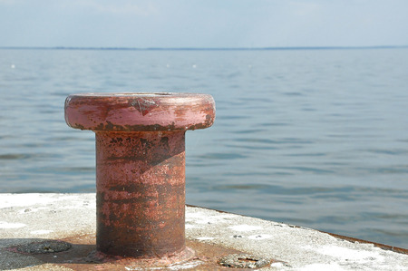 Old rusty steel mooring bollard pole Stock Photo