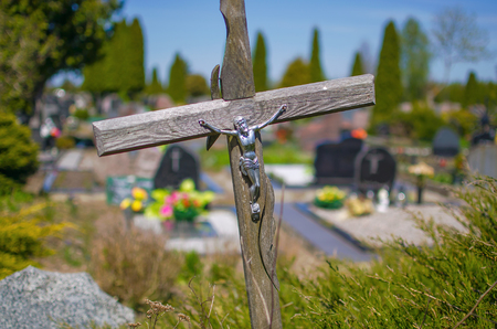 Old wooden cross on a grave in a cemetery