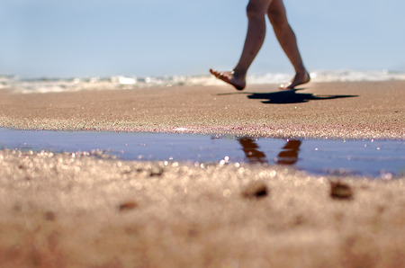Legs on the beach on blue sky and sea background Stock Photo