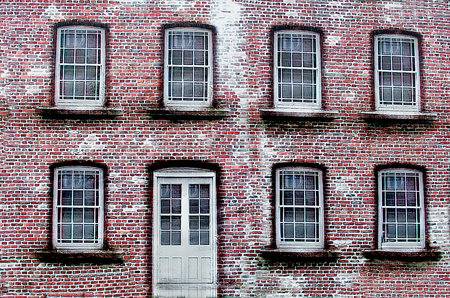 Wall of the old red brick with white door and symmetrical windows