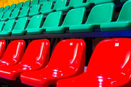 The auditorium in the sports complex with green and rede plastic seats. Places for spectators of a sports match indoors.