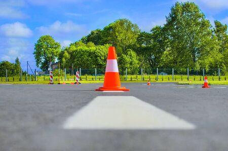 Traffic cone standing on dark asphalt. Red rubber cone in road construction. Road works, parking area.Traffic cone on the airport runway. Cone fence posts on the road for car driving training at the driver training school.