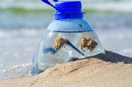 Plastic bottle in beach sand. Plastic pollution of the oceans concept. Package garbage on the shore. Global warming problem. Pet bottle of fresh water is on the sand by the sea.