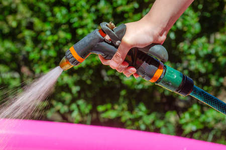 Hand holds a hose with sprayer and watered the plants. Watering grass in the garden in summer from hose with sprinkler. Gun nozzle sprayer with splash on green shrubs background. Gardening concept.