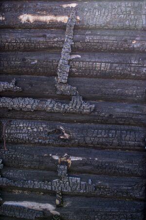black background. Burnt wooden Board texture. Burned scratched hardwood surface. Smoking wood plank background. Burned wooden grunge texture Space for text. Zdjęcie Seryjne