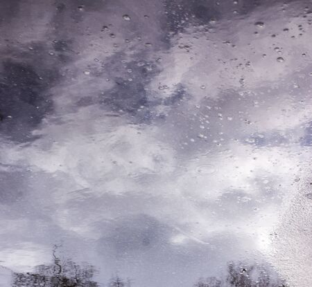 Rain drops rippling in a puddle with buildings, sky and trees reflection