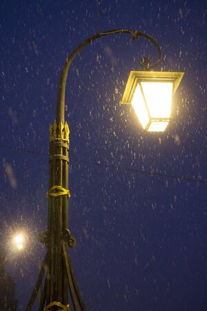 lantern on quay of the bypass channel. Snow is falling. Saint Petersburg Russia