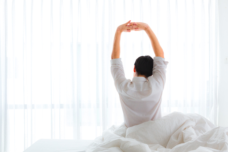 Black hair of young business asian man sitting near the big white window while stretching his arms on bed after waking up with sunrise at morning, back view.